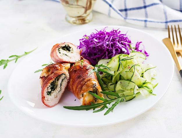 Ketogene diät. abendessen mit hühnerfleischbrötchen wünschen speck und salat mit rotkohl, gurke, rucola. entgiftung und gesundes konzept. keto essen.