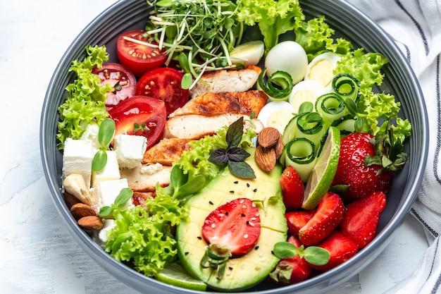Ketogene diät. hühnersalat mit avocado, feta-käse, wachteleiern, erdbeeren, nüssen und salat auf weißem hintergrund. keto-paläo-frühstück. köstliches ausgewogenes lebensmittelkonzept.