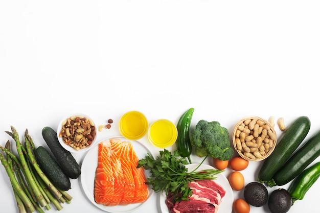 Ketogene ketodiät, einschließlich gemüse, fleisch und fisch, nüsse und öl auf weißem hintergrund mit kopienraum