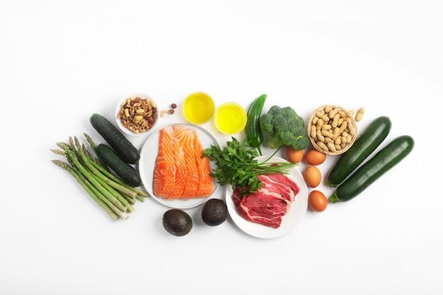Ketogene ketodiät, einschließlich gemüse, fleisch und fisch, nüsse und öl auf weißem hintergrund