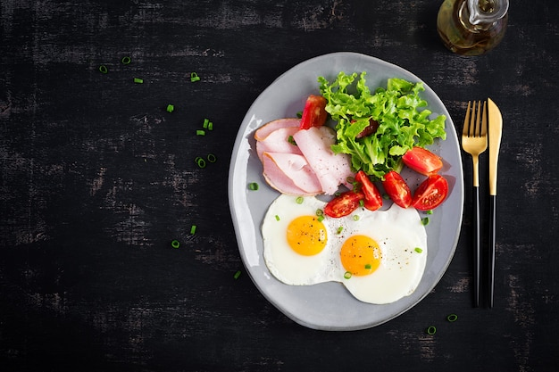 Ketogene / paläo-diät. spiegeleier, schinken und frischer salat. keto frühstück. brunch. draufsicht, oben