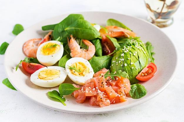 Ketogenes diätfrühstück. salzlachssalat mit gekochten garnelen, garnelen, tomaten, spinat, eiern und avocado.