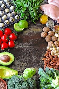 Ketogenes diätkonzept. eine reihe von produkten der kohlenhydratarmen ketodiät. grünes gemüse, nüsse, hähnchenfilet, leinsamen, wachteleier, kirschtomaten. gesundes lebensmittelkonzept. keto diät essen.