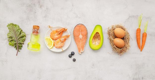 Ketogenes kohlenhydratarmes diätkonzept. zutaten für die auswahl an gesunden lebensmitteln auf weißem betonhintergrund.