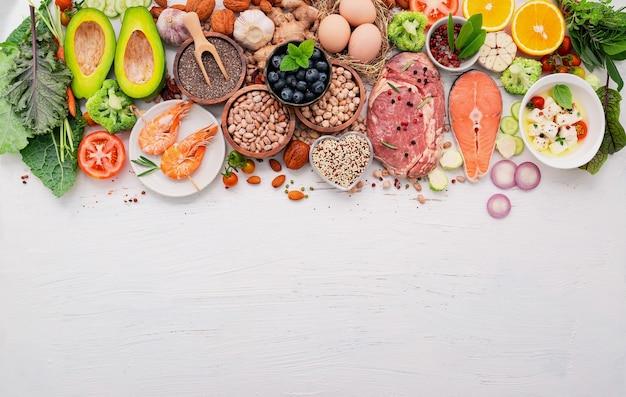 Ketogenes kohlenhydratarmes diätkonzept. zutaten für die auswahl an gesunden lebensmitteln auf weißem holzhintergrund.