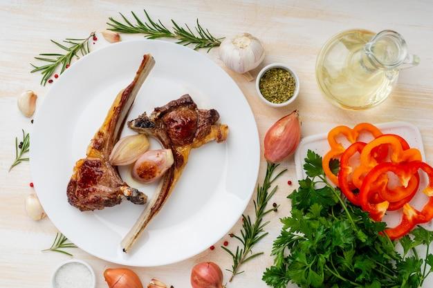 Ketogenic, paleo, lchf diät - fett briet lammrippen auf weißer platte mit gemüse und gewürz