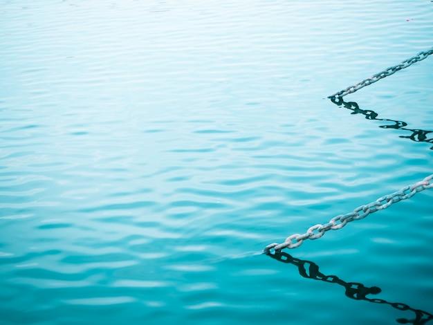 Kette über blauem grünem meerwasser in der strukturstille des seemetalleisens im freien, die b sich fühlt