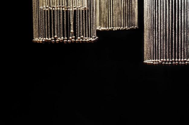 Ketten mit glocken in form von kugeln werden hervorgehoben und hängen in einem kreis auf schwarzem hintergrund.