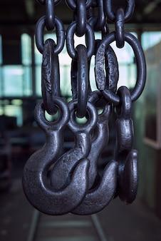 Kettenfrachtschlinge. schwarze stahlkette und frachthaken. abstrakter industrieller hintergrund.