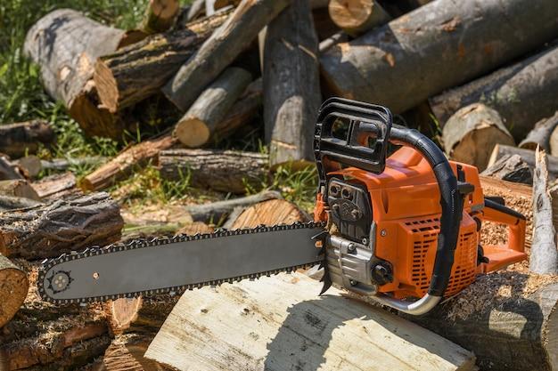 Kettensäge, die auf einem haufen brennholz im hof auf brennholz und bäumen steht, die von einer kettensäge geschnitten wurden