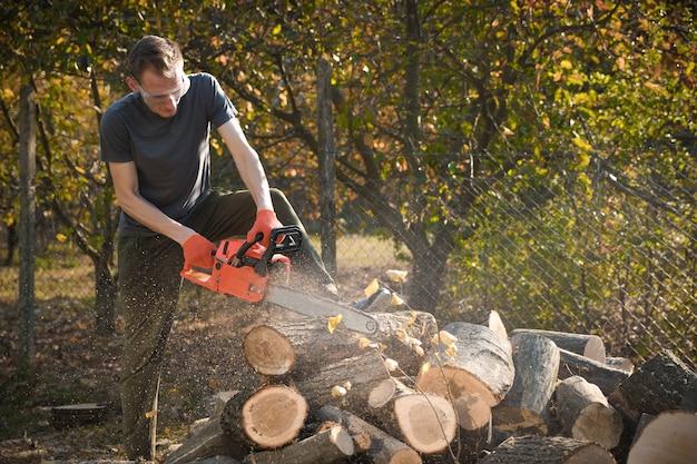 Kettensäge, die auf einem haufen brennholz im hof auf einem schönen hintergrund von grünem gras und wald steht.
