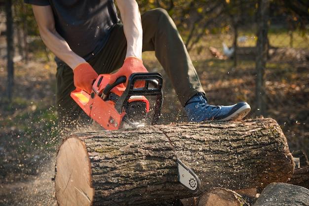 Kettensäge, die auf einem haufen des brennholzes im yard auf einem schönen grünen gras und einem wald steht. holz schneiden mit einem motortester
