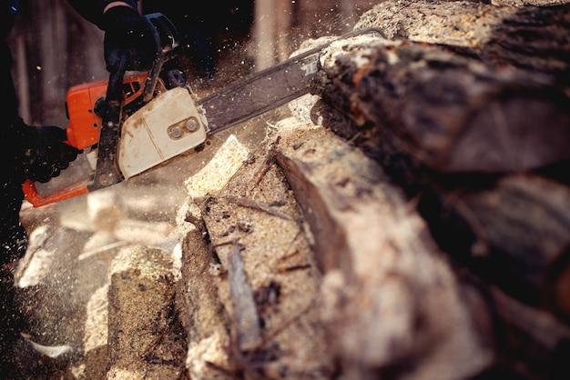 Kettensäge in aktion holz schneiden. mann, der holz mit säge, staub und bewegungen schneidet.