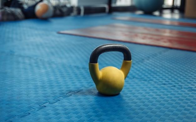 Kettlebell auf dem boden mit blauer gummibeschichtung im fitnessstudio