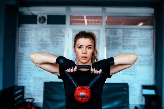 Kettlebell training im fitnessstudio. nahaufnahme des trainings der jungen frau.