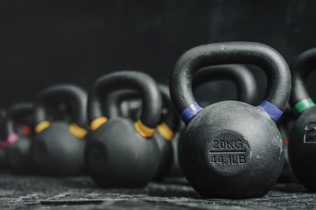 Kettlebells-ausrüstung auf dunklem hintergrund im crossfit-fitnessstudio. sportkonzept. speicherplatz kopieren