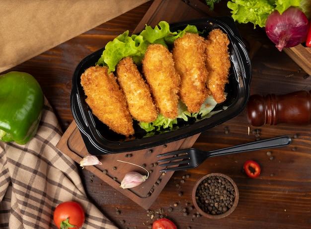 Kfc-art gebratenes hühnernuggets zum mitnehmen im schwarzen behälter