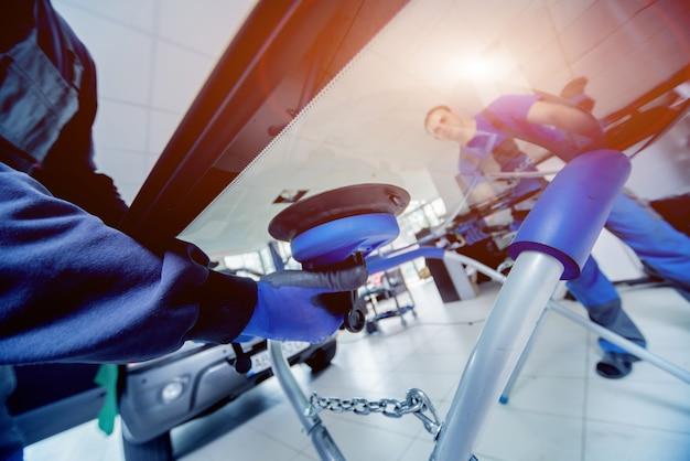 Kfz-spezialarbeiter, die die windschutzscheibe eines autos im autoservice ersetzen