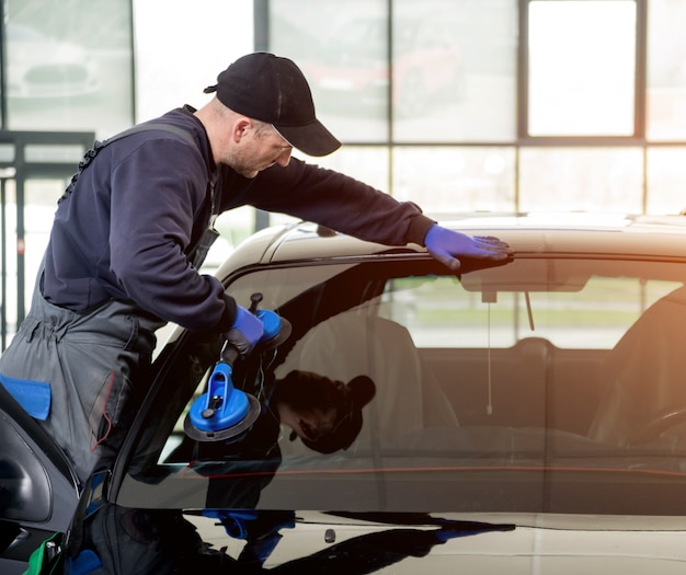 Kfz-spezialarbeiter, die windschutzscheibe oder windschutzscheibe eines autos in der garage der autotankstelle ersetzen.