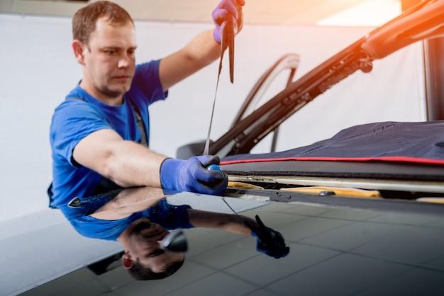 Kfz-spezialarbeiter entfernen alte windschutzscheiben oder windschutzscheiben eines autos in der garage einer autotankstelle.