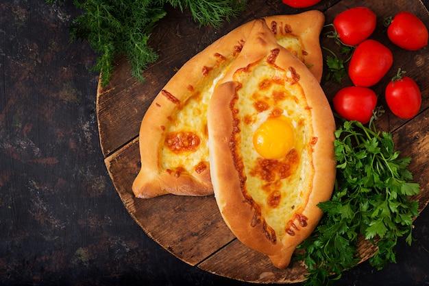 Khachapuri in adjarian. torte mit mozzarella und ei öffnen. georgische küche.