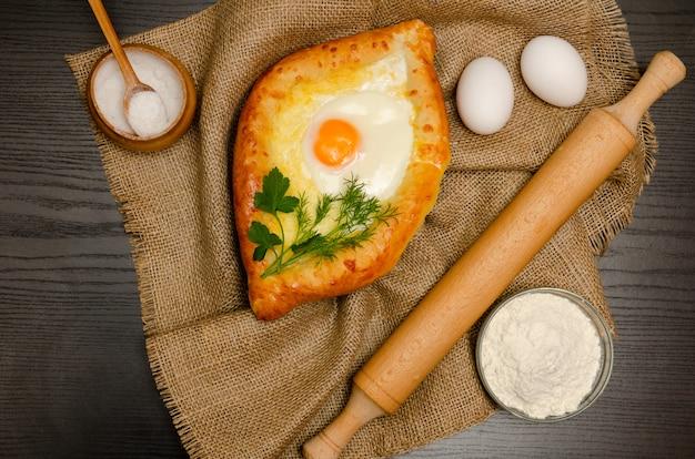 Khachapuri mit eiern auf sackleinen, mehl, eiern und salz auf schwarzer tabelle