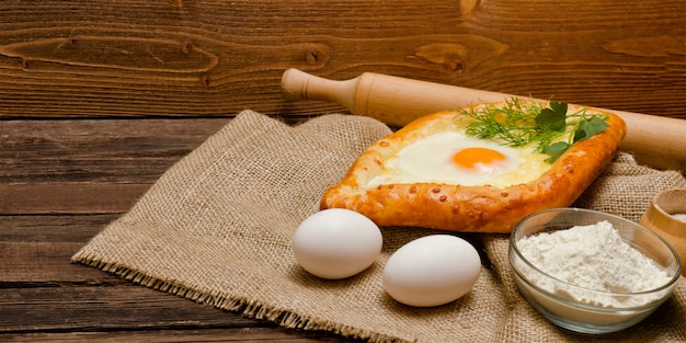 Khachapuri mit eiern auf sackleinen, mehl und eiern