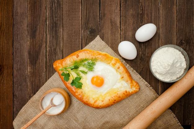Khachapuri mit eiern auf sackleinen, salz, mehl und eiern. holztisch, kopie, raum