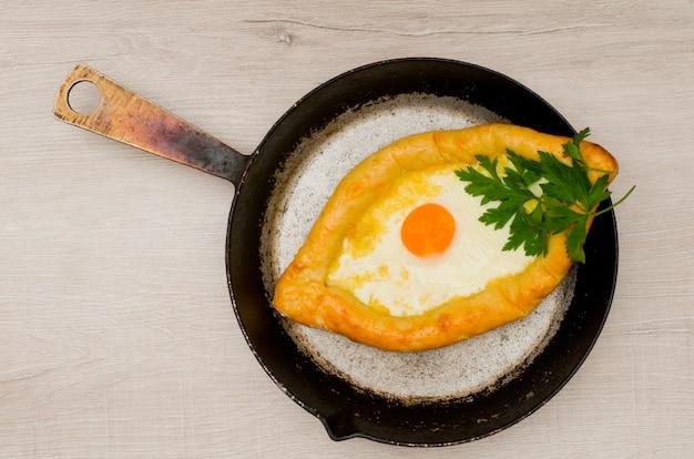Khachapuri mit käse und ei in einer bratpfanne auf einem hellen holztisch