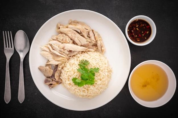 Khao mun gai, thailändisches essen, mit hühnersuppe gedämpfter reis, serviert mit hühnchen, suppe und sauce auf dunklem texturhintergrund, draufsicht