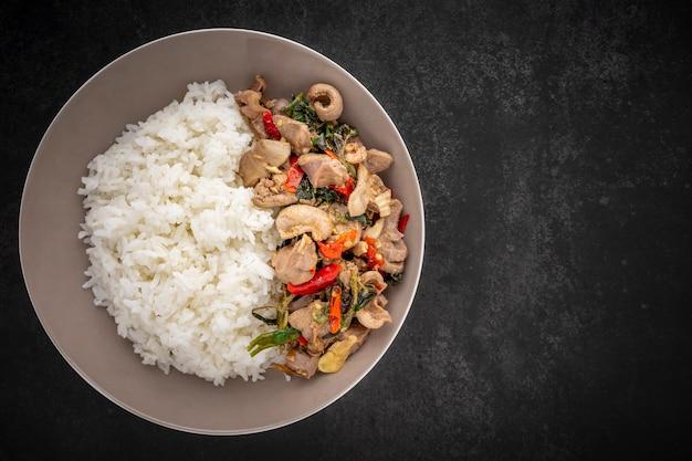 Khao pad ka prao kruang nai gai, thailändisches essen, geströmter reis mit gebratenem basilikum, gebratene hühnernebenprodukte, verschiedene fleischsorten, zupf- oder organfleisch auf dunklem hintergrund mit kopienraum für text, draufsicht