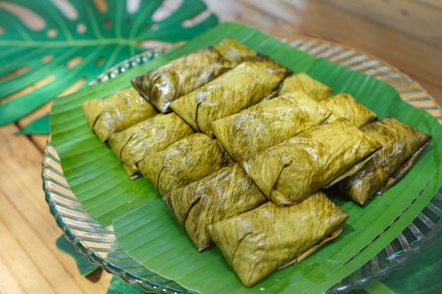 Khao tom verrückte oder gedämpfte mungobohne mit klebreis ist das lokale und traditionelle thailändische dessert. es ist von bananenblättern umwickelt.