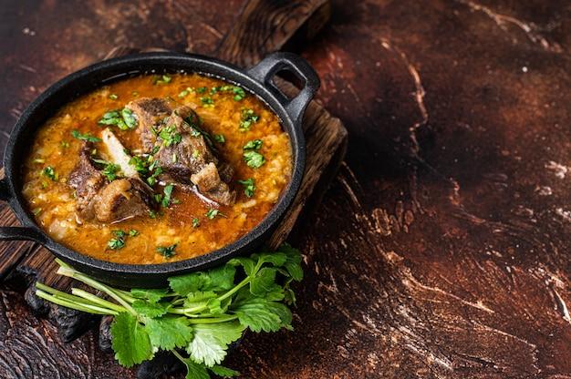 Kharcho suppe mit lammfleisch, reis, tomaten, karotten, paprika, walnüssen und gewürzen.