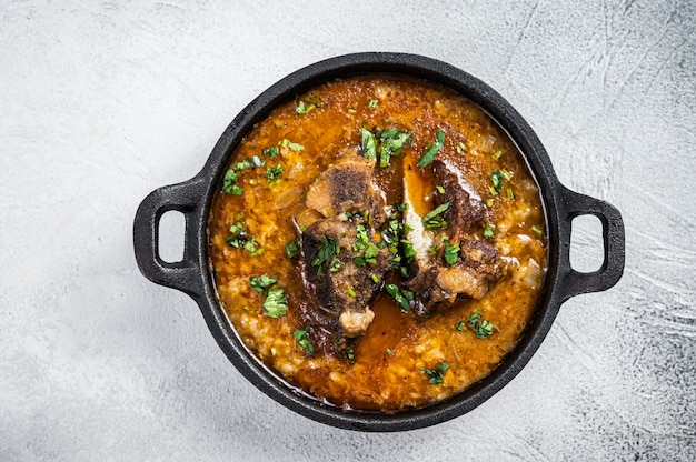 Kharcho-suppe mit rindfleisch, reis, tomaten und gewürzen in einer pfanne.