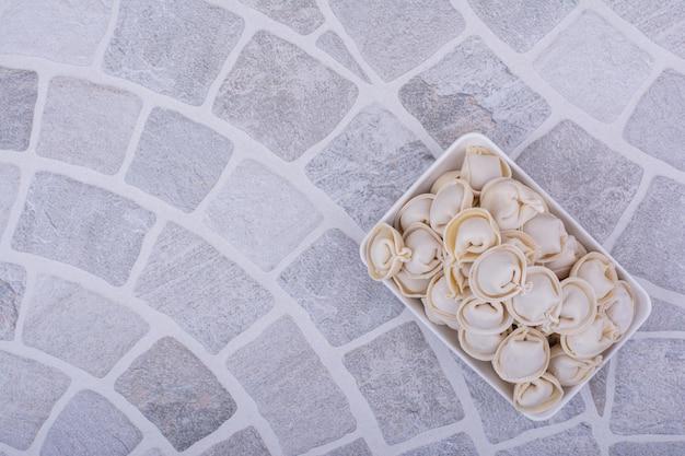 Khinkali-teig mit füllungen und gehackten kräutern in einer weißen schüssel.