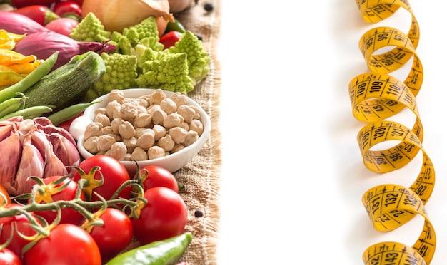 Kichererbse und rohes gemüse mit maßband lokalisiert auf weißer nahaufnahme