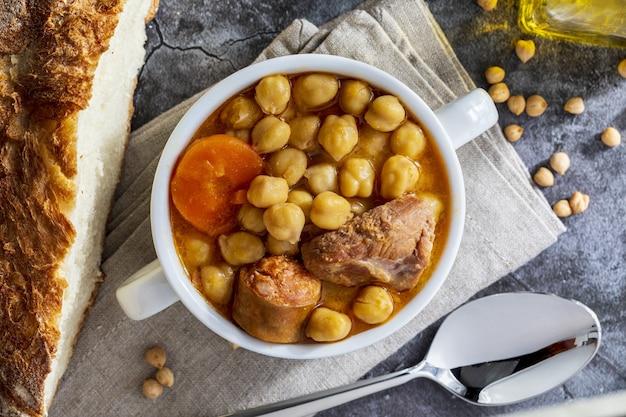 Kichererbsen-eintopfgericht (madrid-eintopf). mit rindfleisch, chorizo, speck, karotten und olivenöl. mittelmeerküche. hausgemachter look. draufsicht.