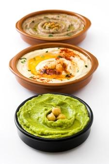 Kichererbsen-hummus, avocado-hummus und linsen-hummus lokalisiert auf weiß