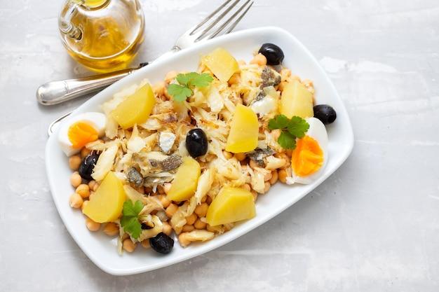 Kichererbsen mit kabeljau, oliven und gekochtem ei in weißer schale auf keramikhintergrund