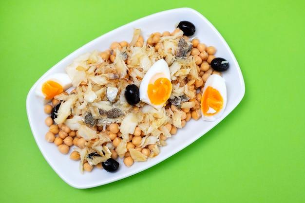 Kichererbsen mit kabeljau-oliven und gekochtem ei in weißer schale