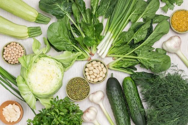 Kichererbsen, mungobohnen und nüsse in schalen. frische spinatblätter und dill. kohl, gurken und zucchini auf dem tisch. weißer hintergrund. flach liegen.