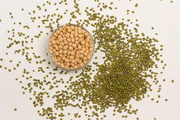 Kichererbsen- und mungobohnenbohnen auf weißem hintergrund. quelle für natürliches eiweiß, vitamine und mineralien. Premium Fotos
