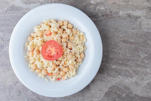 Kichererbsen und nudeln mit tomatenscheiben auf dem teller, auf dem marmor.