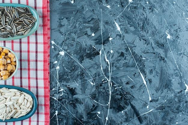 Kichererbsen und sonnenblumenkerne auf schalen auf dem geschirrtuch, auf dem blauen tisch.