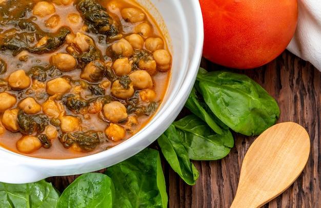 Kichererbseneintopf mit spinat (potaje). köstliches löffelgericht für herbst und winter. traditionelles essen. vordergrund.