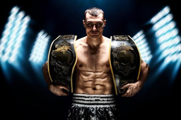 Kickbox-weltmeister im mittelgewicht steht mit zwei gürteln. das konzept eines gesunden lebensstils, sieg, erfolg. motivation. gemischte medien