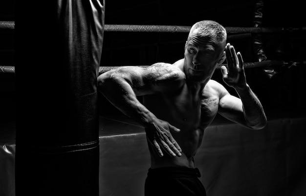 Kickboxer ellbogen auf der tasche im fitnessstudio. das konzept von sport, gemischten kampfkünsten. gemischte medien