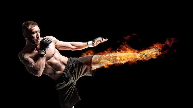 Kickboxer posiert im ring. mittlerer tritt mit einem brennenden fuß. das konzept von mma, wrestling, muay thai. gemischte medien