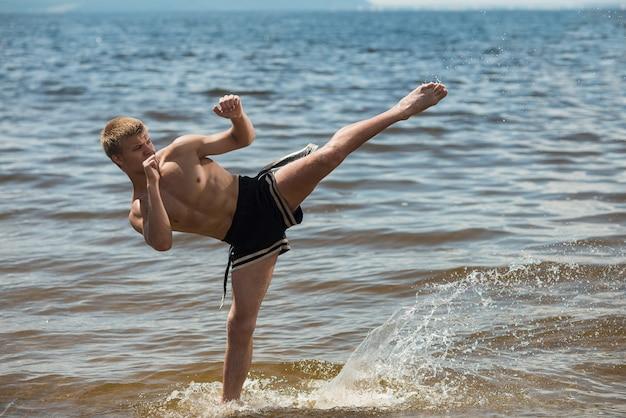 Kickboxer tritt im sommer unter freiem himmel gegen das meer.