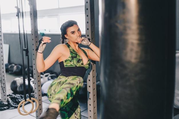 Kickboxing frau, die kicking bag im fitnessstudio schlägt. crossfit. fitnessfrau.
